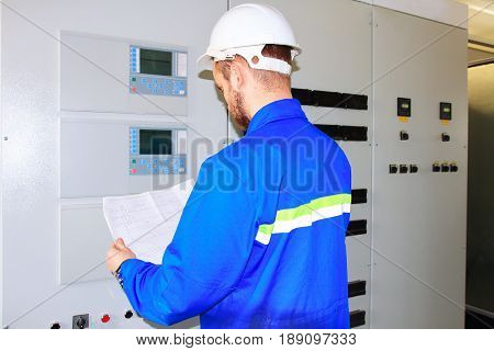 specialist of the industrial complex looks at the drawing of the electrical diagram of the automation cabinets. Specialist in special clothes. Specialist in white helmet and uniform