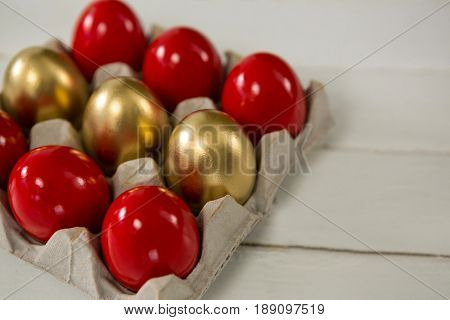 Close-up of red and golden Easter eggs in the carton on wooden background