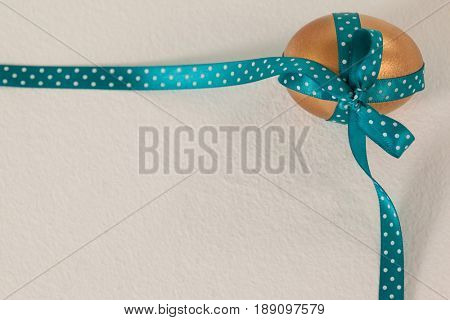 Golden easter egg tied with blue ribbon against white background