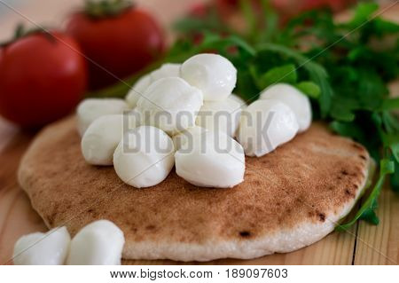 Pita Bread With Mozzarella, Greens And Tomatoes. Israeli National Pastries On Wooden Background. Clo