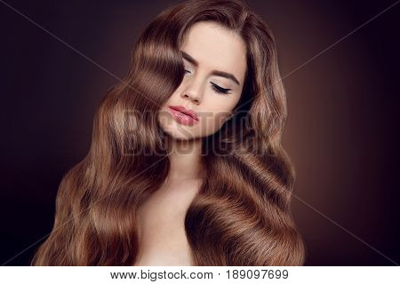 Beauty Hair. Brunette Girl With Long Shiny Wavy Hair. Beautiful Model Portrait With Curly Hairstyle