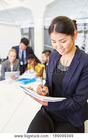 Asian woman as consulting manager writing and taking notes for control