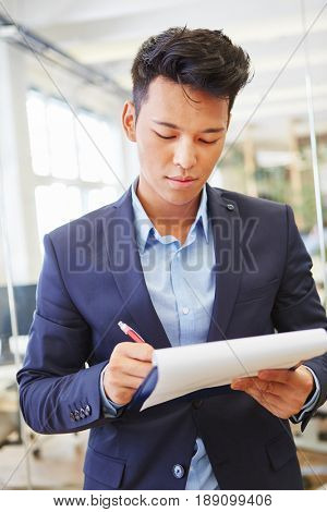 Consultant writing on his checklist and controls business plan