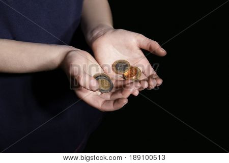 Hands of poor little girl with coins on black background