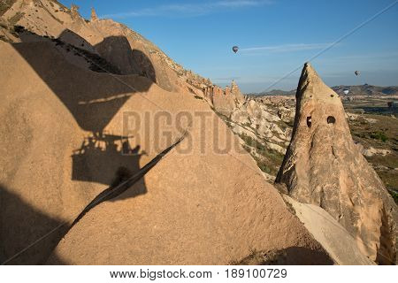 Hot-air balloon flying over Cappadocia rocks. Hot-air balloon shadow on rock is in foreground.
