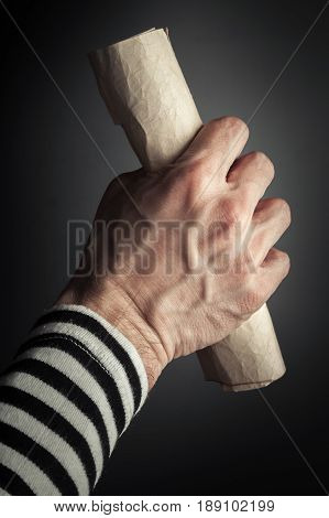 Strong Sailor Hand Holds Rolled Old Crumpled Paper