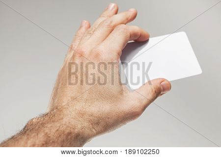 Male Hand Holds White Empty Card On Gray Wall