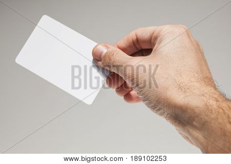 Male Hand With White Empty Card Over Gray Wall
