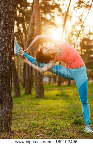Athlete in sportswear during training in morning at park. Sunflare effect