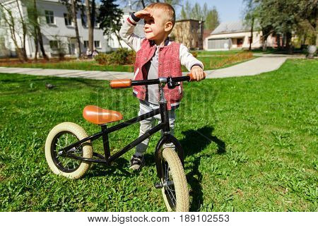 Boy with balane bike on green lawn in park during day