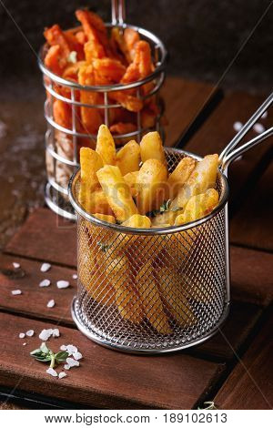 Variety of french fries traditional potatoes, sweet potato, carrot served in frying basket with salt, thyme on wooden board over brown texture background. Homemade fast food