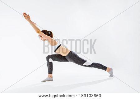 Sports brunette doing gymnastics on blank background