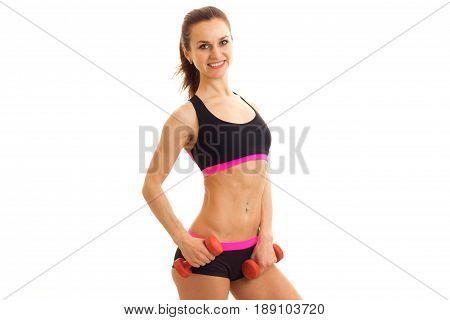 a svelte young fitness girl with beautiful waist smiling looks at the camera and holding a dumbbell is isolated on a white background