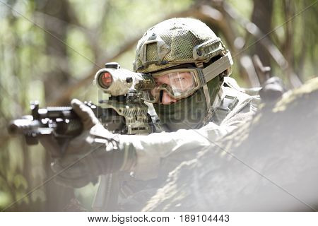 Soldier with airsoft automatic rifle with telescopic sight in forest