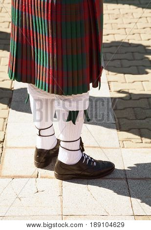 Red and green tartan Scottish kilt. Highlander wearing Scotland traditional clothes. Bagpiper uniform - skirt and knee socks