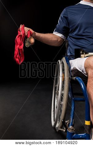 Cropped View Of Paralympic Sitting In Wheelchair And Holding Gold Medals Isolated On Black