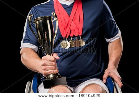 Cropped View Of Paralympic In Wheelchair With Champion Goblet And Gold Medals Isolated On Black