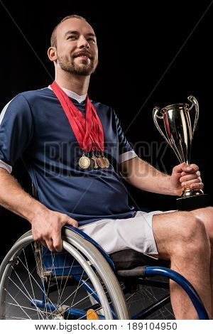 smiling paralympic in wheelchair with gold medals on neck holding champion goblet isolated on black