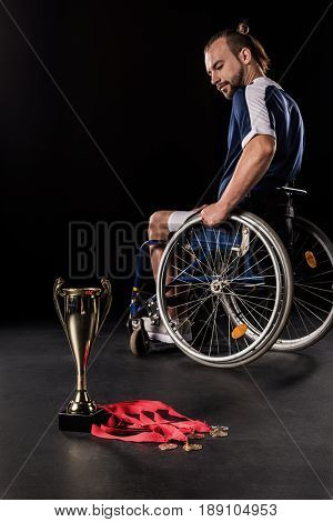 upset paralympic in wheelchair looking at champion goblet and gold medals isolated on black