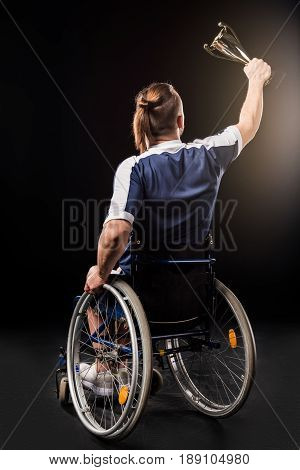 Rear View Of Paralympic Sitting In Wheelchair And Holding Champion Goblet Isolated On Black