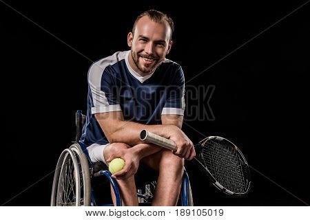 Smiling Young Man In Sportswear Sitting In Wheelchair And Holding Tennis Racquet With Ball