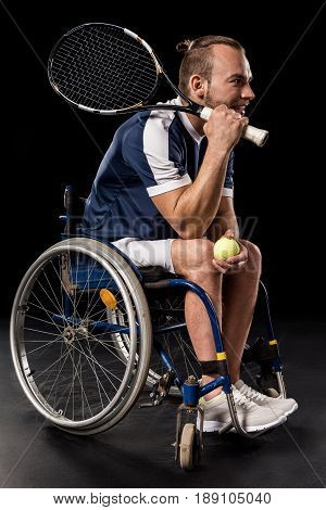 Disabled Young Sportsman In Wheelchair Holding Tennis Racquet With Ball And Looking Away