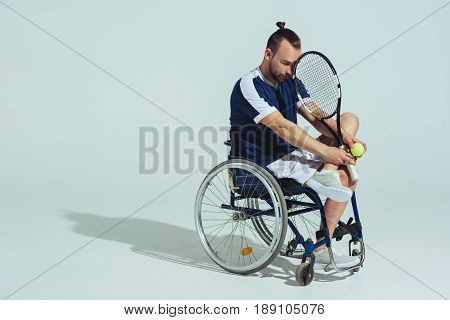 Upset Tennis Player Sitting In Wheelchair And Holding Tennis Racquet And Ball Isolated On Grey