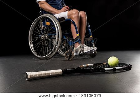 Close-up View Of Tennis Racquet With Ball And Disabled Sportsman Sitting In Wheelchair Behind