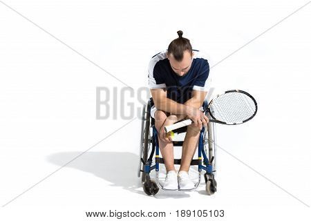 Disabled Young Man Sitting In Wheelchair And Holding Tennis Racquet Isolated On White