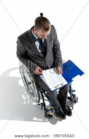 Young Physically Handicapped Businessman In Wheelchair Looking At Contract