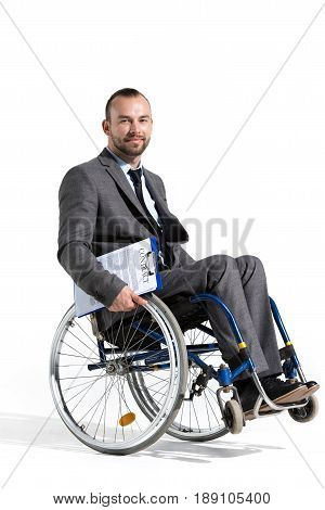 Physically Handicapped Businessman In Wheelchair Looking At Camera With Contract