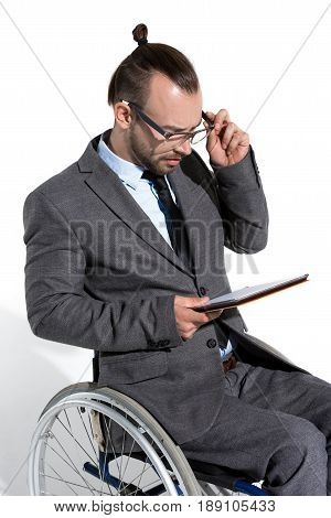 Young Physically Handicapped Businessman In Wheelchair Using Digital Tablet