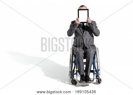 Physically Handicapped Businessman In Wheelchair With Digital Tablet Isolated On White