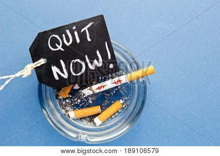 Stop Smoking - Quit Now - with cigarettes, ashtray and blackboard on blue background