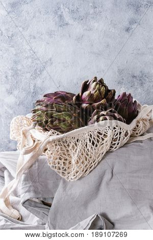 Uncooked whole organic wet purple artichokes in knitted bag on white tablecloth over gray texture background.