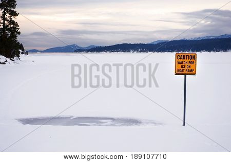 Caution: Watch for Ice on Boat Ramp sign buried in snow and ice on Flathead Lake, Montana