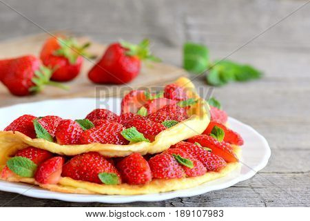 Fresh strawberry egg omelette. Omelette filled with strawberries slices and garnished with mint leaves on a plate. Fresh strawberries on a wooden table. Clean eating sweet breakfast omelette recipe