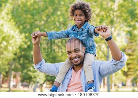 Smiling father holding his son on shoulder and looking at camera. Portrait of happy african dad little boy smiling in the garden. Black father giving his son piggyback at park.
