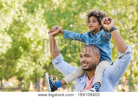 Father giving son ride on back at park. Portrait of happy african father giving son piggyback ride on his shoulders and looking up. Cute black boy with dad playing outdoor. Father day concept.