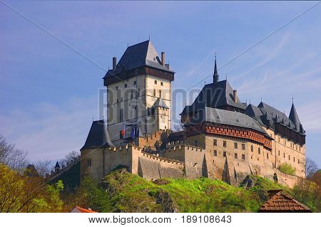 View on famous Czech castle on rock Karlstejn in Gothic style architecture with tall stone cascade walls, towers and loopholes. Traditional european castle architecture. Czech holidays vacations