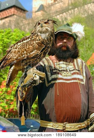 CZECH REPUBLIC, APR, 29, 2017: Brown owl is seating on man hand at Karlstejn castle. Man in traditional classic Czech suit costume. Beautiful wild owl. Famous sightseeing places holidays vacations