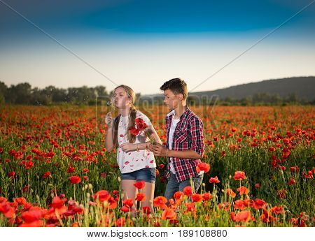 Teen Boy And Girl Posing On The Poppy Field