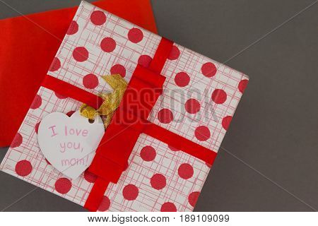 Close-up of gift box with I love you mom tag on grey background