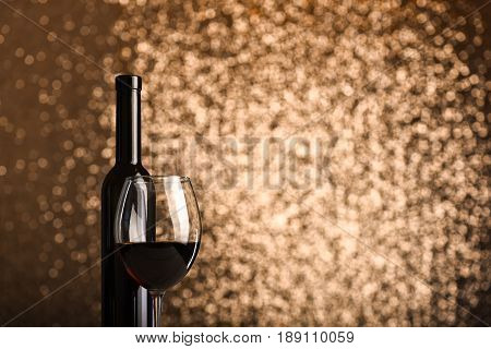 Wine in glass near bottle on sparkling metallic background with copy space. Minimalistic concept of celebration toast