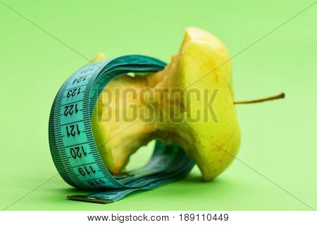 Concept of diet vitamin nutrition and healthy lifestyle: bitten apple lying on side wrapped with greenish blue flexible ruler on light green background