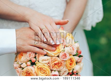 Hands of newlyweds and rings on a wedding bouquet