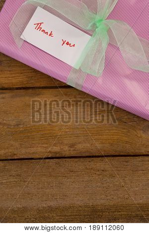 Thank you card with gift box on wooden table