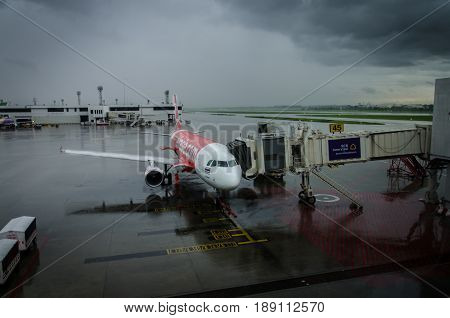 Air Asia Thailand - 21 May 2017: Airasia airplane parked at Don Muang while raining AirAsia is a Malaysian low-cost airline headquartered near Kuala Lumpur Malaysia. The meaning of the Thai text in the picture is Siam Commercial Bank.