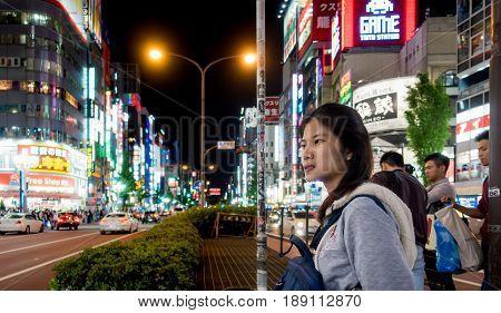 Tokyo Japan - May 5 2017: A girl is crossing Shinjuku shopping street.