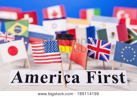 American flag is in front of the slogan America First and many flags of other countries.